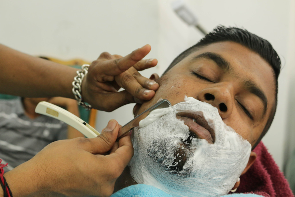 Thishen Pillay receiving a close shave by the owner Mahesh Maisuriyu in the busy Five Star unisex hair salon on Mint Street. Five Star is one of the many foreign owned hair salons in the area Photo: Tanisha Heiberg