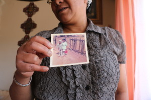 Faieza holds an image of herself and her broher when they were younger. The picture shows the style f clothing that Malay people would wear during the 70's. These were mostly formal suits and dresses with the kufi cap and dresses that covered the knees. today many young people wear wat is fashionable and trending instead of what is traditional. Photo: Rafieka Williams