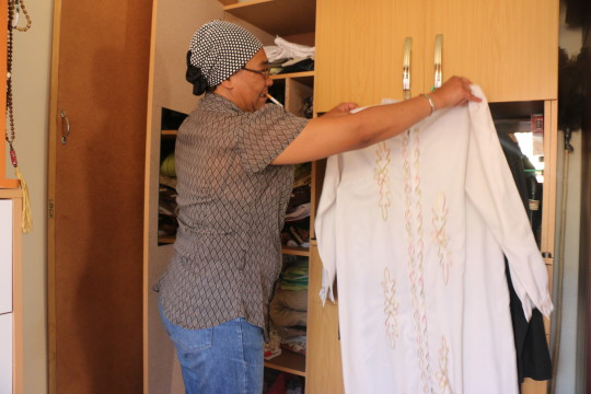 Faieza demonstrates the traditional wear that Malay women would hand sew and embroid on their own for celebrations such as gadats and for madressah (muslim school). She still preserves and holds onto these garments that she was raised in so she can remember the days when Malay culture was thriving in Fietas, Johannesburg. Today young Malay people just buy abayas. photo: Rafieka Williams
