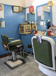 GREEN BACKS: The Majestic Barber in Fordsburg is home to many photographs and antiques such as the worn leather green cutting chairs. The tiny shop once held five barbers chairs, but now only two remain after they were sold to antique collectors. Photo: Tanisha Heiberg
