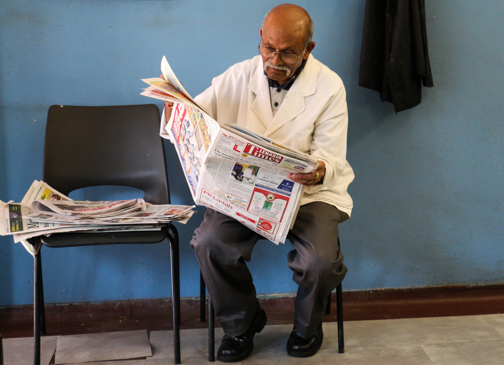 Chhagan Cgopal spends most of his time paging through the local newspapers that he piles up on the chair next to him, while waiting for customers to come to his now quiet barbershop in Fordsburg. Photo: Tanisha Heiberg