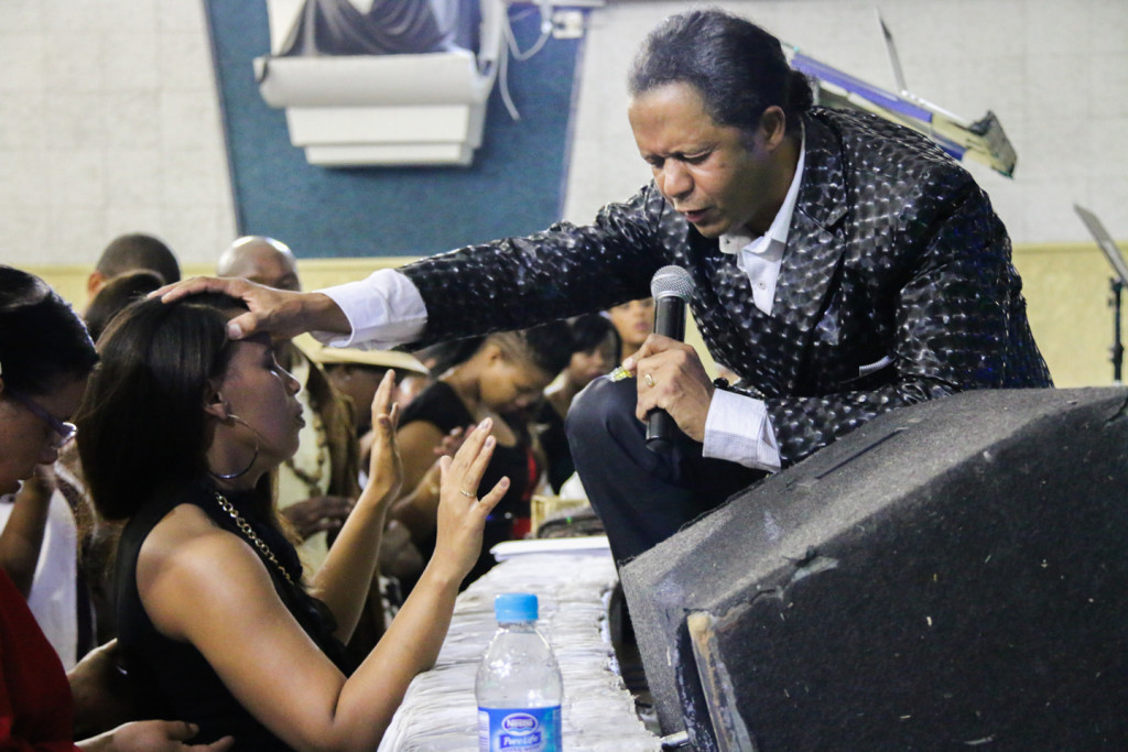 Pastor Mark Bismark lays his hand on a young ladies head as a blessing for her exams. Photo: Katleho Sekhotho