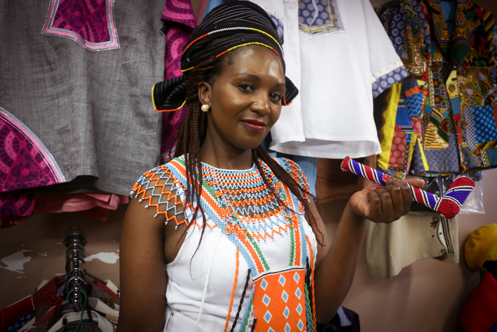 The manager of KwanNtu Afrocentric Designs, Vicky Ginya wearing a traditional Xhosa attire (isikhakha), a red, white and yellow beaded black head-doek (isikhetshemiya) complemented with a vibrant and colourful bead work (uvelibhoyi) and a beaded smoking pipe (inqawa) at KwaNtu store in Oriental Plaza. Photo: Litaletu Zidepa