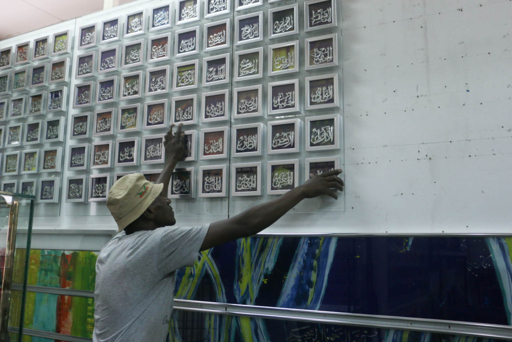 A factory workr at the Orient Art gallery putting up one of their most popular installation pieces, the 99 names of Allah.