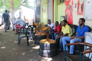 A group of men sitting outside Ali's coffee shop with his son, Farhaan Ebrahim Mohammed. Photo: Sinikiwe Mqadi