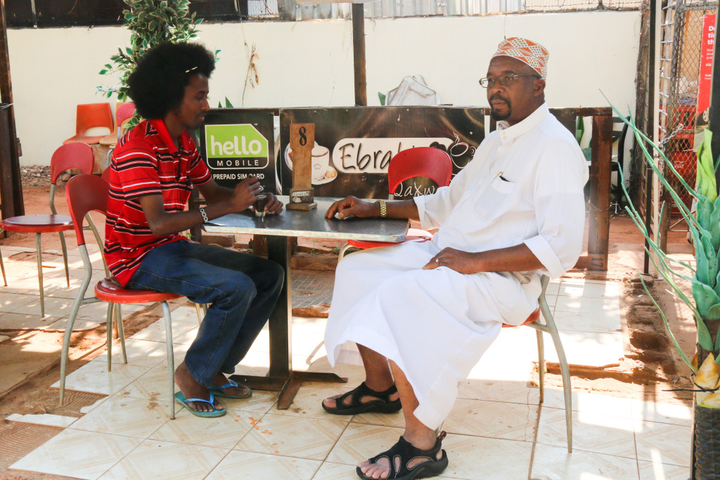 Ali sitting with Am Ahmed, the Chairperson of the Somali Culture and Heritage Council during his visit in Ali's coffee shop. He is drinking a cup of qakwo. Photo: Sinikiwe Mqadi
